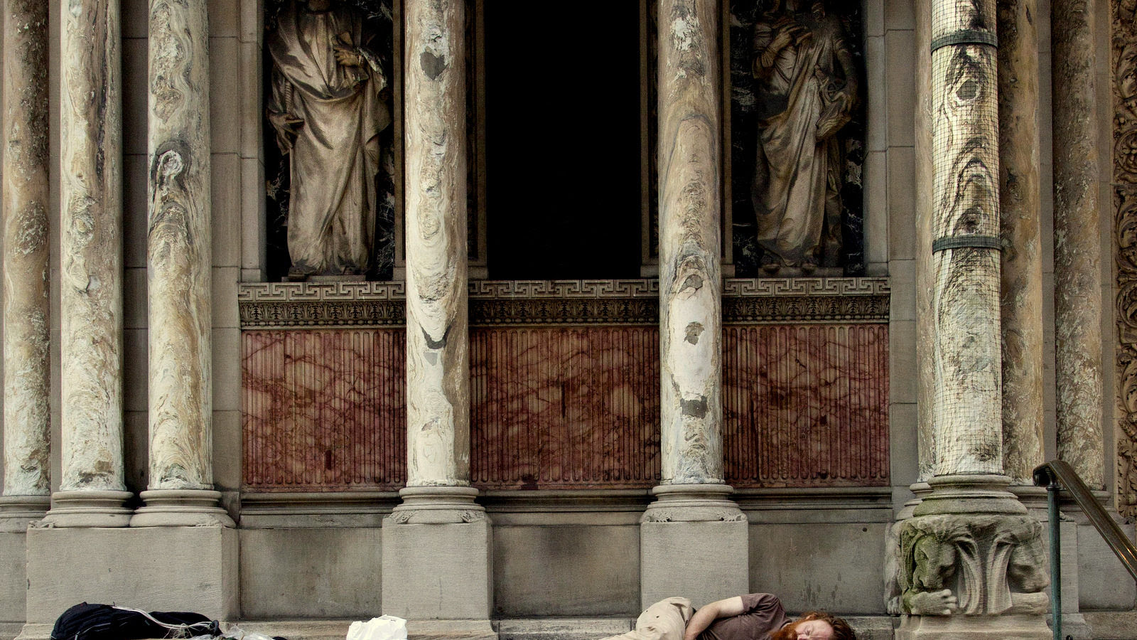 A Homeless man sleeps on the steps of St. Bartholomew's Church