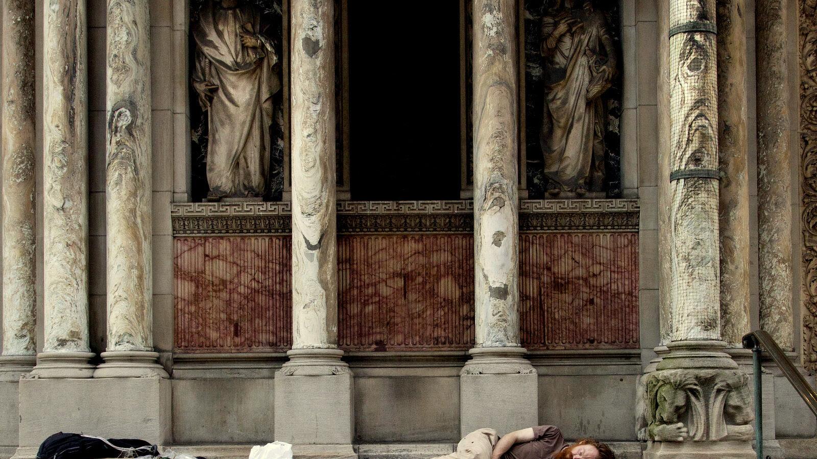 A Homeless man sleeps on the steps of St. Bartholomew's Church