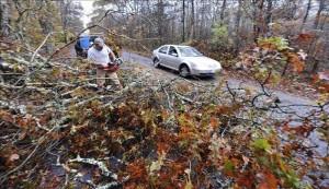 Un hombre corta ramas de árboles caídos tras el paso del huracán Sandy por Westport en Massachusetts (Estados Unidos). EFE.