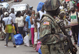 A Liberian soldier, right, scans people for signs of the Ebola virus, as they control people from entering the West Point area in the city of Monrovia, Liberia, Saturday, Aug. 23, 2014. (AP Photo/Abbas Dulleh)