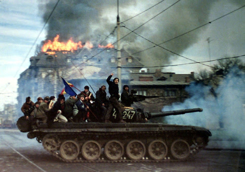 "Exactly 25 years ago, the last removal of a Communist regime in a Warsaw Pact country. Bucharest, Romania, 1989. via reddit[[MORE]]mega002:Some info and background of the revolution:The total number of deaths in the Romanian Revolution was 1,104. The number of wounded was 3,352.In 1981, Ceaușescu began an austerity program designed to enable Romania to liquidate its entire national debt ($10 billion). To achieve this, many basic goods, including gas, heat and food were rationed, which drastically reduced the standard of living in Romania. The secret police (Securitate) had become so ubiquitous as to make Romania essentially a police state. Free speech was limited and opinions that did not favor the Communist Party were forbidden. Even by Soviet bloc standards, the Securitate was exceptionally brutal.Protests started on 17 December. Since Romania did not have riot police (Ceaușescu, who genuinely believed that the Romanian people loved him, never saw the need for them), the military were sent in to control the riots because the situation was too large for the Securitate and conventional police to handle. However, the chief of minister of defense, sent soldiers in without live ammunition. The army failed to establish order.The next day, trains loaded with workers originating from factories in the South arrived. The regime was attempting to use them to repress the mass protests, but after a brief encounter they ended up joining the protests. One worker explained: ""Yesterday, our factory boss and a Party official rounded us up in the yard, handed us wooden clubs and told us that Hungarians and 'hooligans' were devastating Timișoara and that it is our duty to go there and help crush the riots. But I realized that wasn't the truth.""On the morning of 21 December Ceaușescu addressed an assembly of approximately 100,000 people, to condemn the uprising in Timișoara. Party officials took great pains to make it appear that Ceaușescu was still immensely popular. He blamed the Timișoara uprising on ""fascist agitators."" However, Ceaușescu was out of touch with his people and completely misread the crowd's mood. The people remained unresponsive, and only the front rows supported Ceaușescu with cheers and applause. Eight minutes into the speech, some in the crowd actually began to jeer, boo, whistle and utter insults at him. The entire speech was being broadcast live around Romania, and it is estimated that perhaps 76% of the nation was watching. Censors attempted to cut the live video feed, and replace it with Communist propaganda songs and video praising the Ceaușescu regime, but parts of the riots had already been broadcast and most of the Romanian people realized that something unusual was in progress.The jeers and whistles soon erupted into riot; the crowd took to the streets, placing the capital, like Timișoara, in turmoil.At approximately 09:30 on the morning of 22 December, Vasile Milea, Ceaușescu's minister of defense, died under suspicious circumstances. A communiqué by Ceaușescu stated that Milea had been sacked for treason, and that he had committed suicide after his treason was revealed. The most widespread opinion at the time was that Milea hesitated to follow Ceaușescu's orders to fire on the demonstrators, even though tanks had been dispatched to downtown Bucharest that morning. Milea was already in severe disfavour with Ceaușescu for initially sending soldiers to Timișoara without live ammunition. The rank-and-file soldiers believed that Milea had actually been murdered, and went over virtually en masse to the revolution. The senior commanders wrote off Ceaușescu as a lost cause and made no effort to keep their men loyal to the regime. This effectively ended any chance of Ceaușescu staying in power."