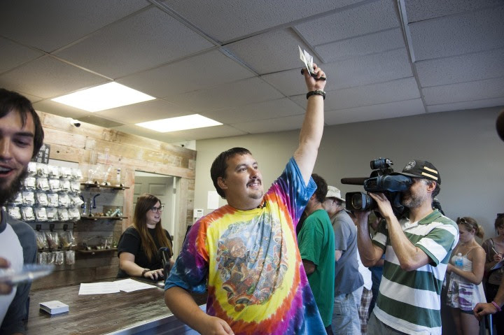 Image: Mike Boyer turns to the crowd outside, showing off the 4 grams of marijuana he bought as the first in line to legally purchase marijuana at Spokane Green Leaf