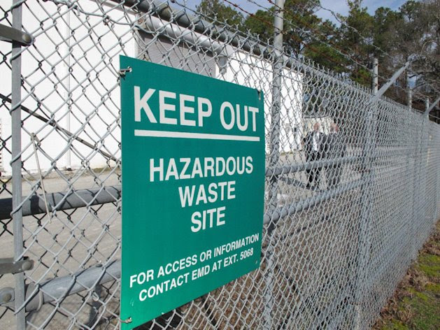"""A sign cautions visitors outside a """"pump and treat"""" facility on the Marine base at Camp Lejeune, N.C., on Wednesday, Feb. 27, 2013. The sprawling installation is the site of one of the worst drinking water contaminations in U.S. history. (AP Photo/Allen Breed)"""