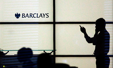 A man gestures whilst speaking on a phone at Barclays Bank in  Canary Wharf in London