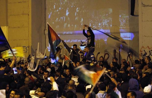Palestinos celebram em Belém, na Cisjordânia, próximo à barreira de separação com Israel, a vitória diplomática desta quinta-feira (29) (Foto: AP)