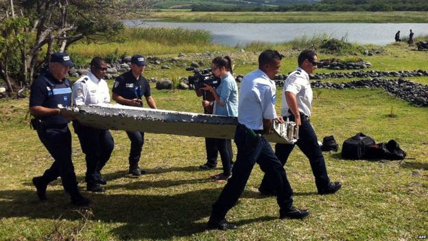 Police carry a piece of debris from an unidentified aircraft found on the French Indian Ocean island of Reunion