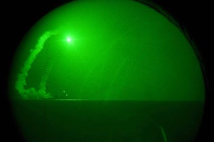 Seen through night-vision lenses, guided missile destroyer USS Barry fires Tomahawk cruise missiles in the Mediterranean Sea.