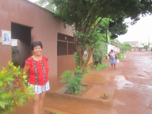 Bernardete Batista de Araujo stands in front of the house where she was relocated in Palmas, together with others displaced by the Lajeado hydroelectric dam in central Brazil. The high walls and a street muddy because of the rain make her miss Vila Canela, her old village on an island that no longer exists on the Tocantins River. Credit: Mario Osava / IPS