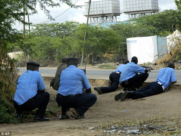Kenyan police officers, pictured, take cover across from the university during the terrorist gun attack