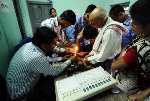 Election officials sealing an electronic voting machine with wax after polling came to an end in Tezpur, Assam, on Monday.