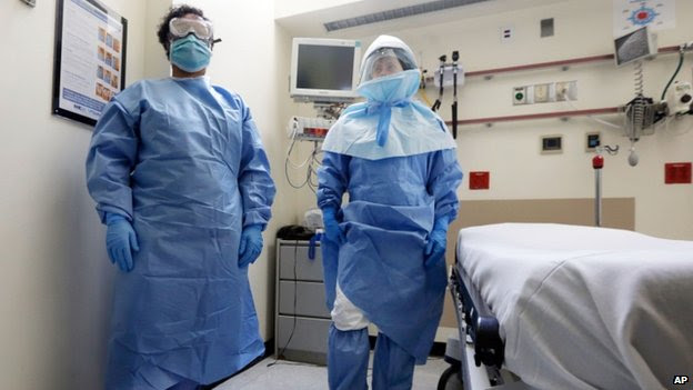 New York's Bellevue Hospital staff in protective suits in an isolation room during a demonstration of procedures for possible Ebola patients