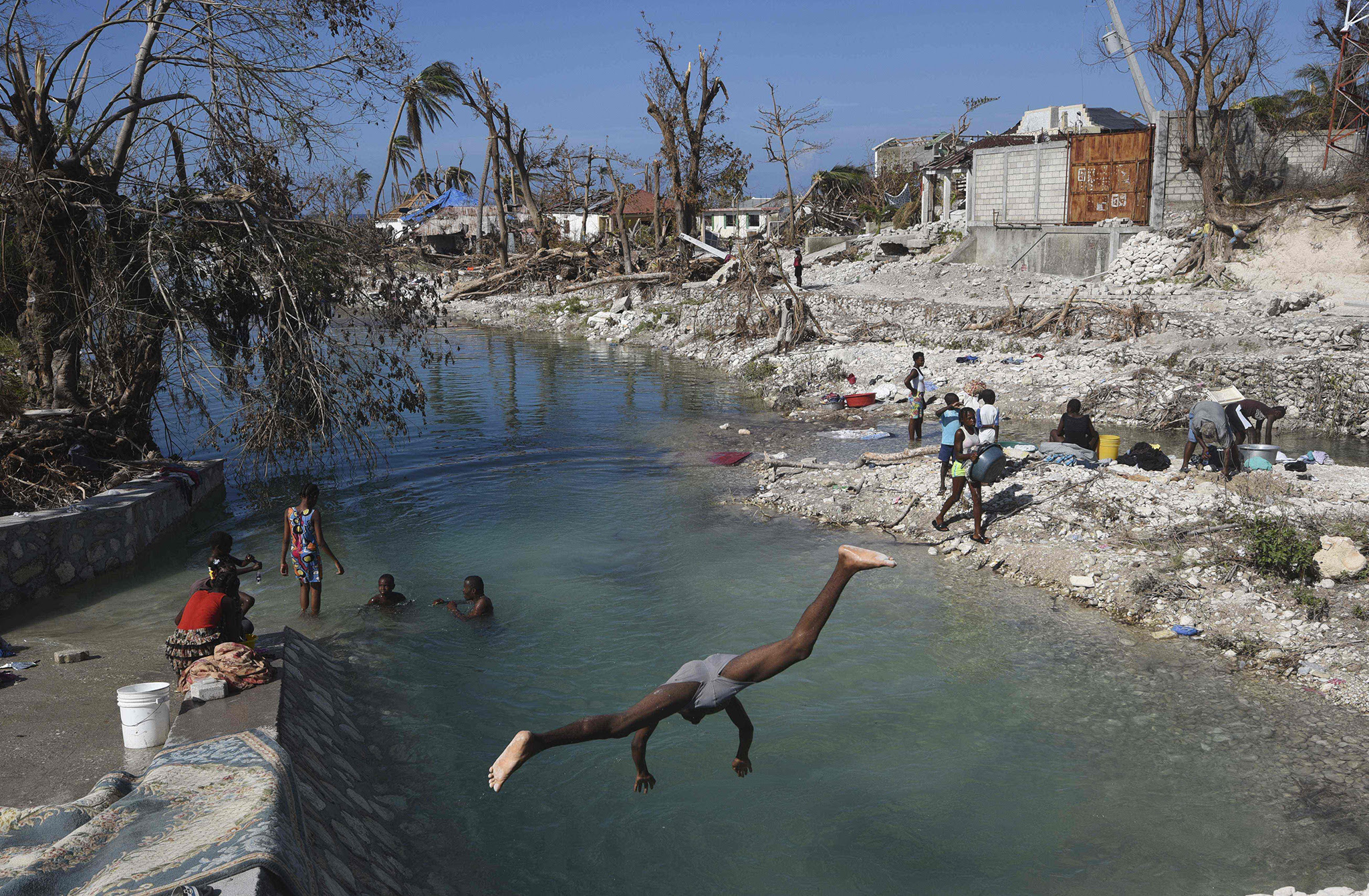 Locals wash clothes in Port Salut southwest of Port-au-Prince, on October 12, 2016, following the passage of Hurricane Matthew. A week after Matthew tore through the country, many remote areas communities were still left to their own devices. Families with destroyed homes and shattered livelihoods waited and prayed for help.   / AFP PHOTO / RODRIGO ARANGUARODRIGO ARANGUA/AFP/Getty Images