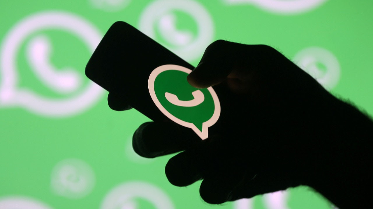 A man poses with a smartphone in front of displayed Whatsapp logo in this illustration September 14, 2017. Image: Reuters.