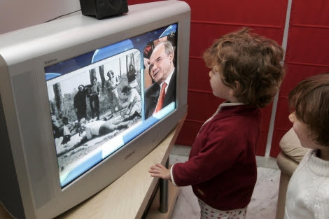Dos niños atentos a las noticias de la televisión. | E. Lobato