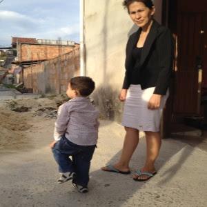 Em imagem de junho deste ano, a mãe de Eliza Samudio, Sônia Moura, aparece na porta de casa com o neto de 2 anos; atualmente, a criança vive com a avó