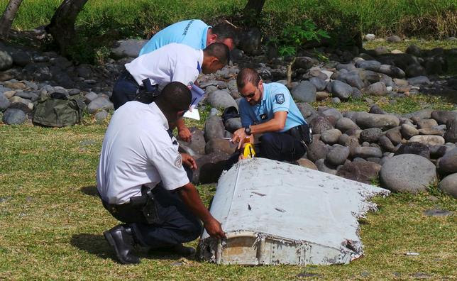 French gendarmes and police inspect a large piece of plane debris which was found on the beach in Saint-Andre, on the French Indian Ocean island of La Reunion, July 29, 2015. REUTERS/Zinfos974/Prisca Bigot