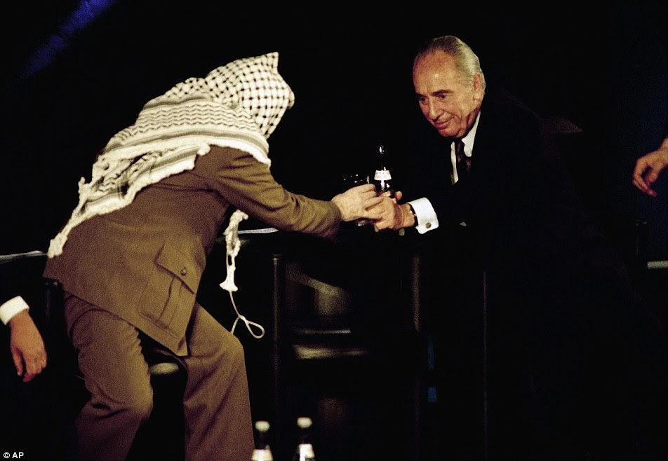 Shimon Peres derrama a água em um copo e as mãos para o líder palestino Yasser Arrafat em um simpósio sobre o Oriente Médio na UNESCO em Paris em 1995