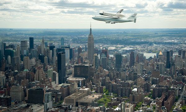 With the Empire State Building in the background, the shuttle Enterprise, mated atop NASA 905, flies above New York City on April 27, 2012.