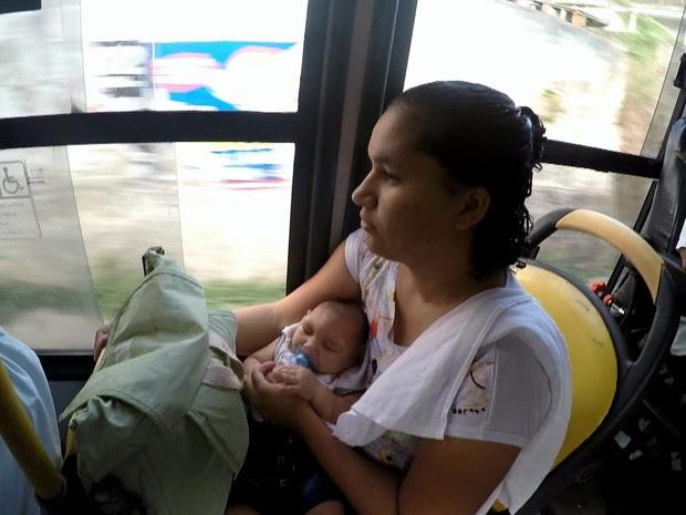Uma mãe carrega o bebê no colo dentro de um ônibus.