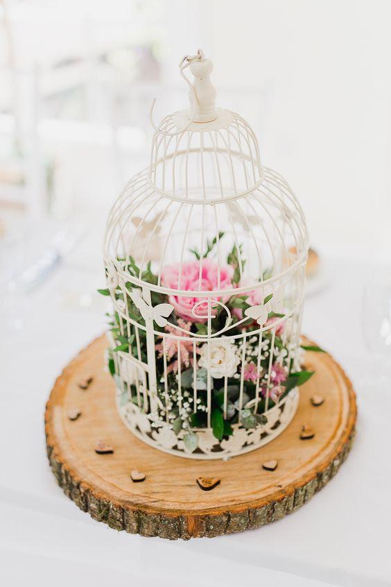 einen weißen Käfig auf einer hölzernen Scheibe mit rosa und weißen Blüten im inneren für eine Rustikale Hochzeit