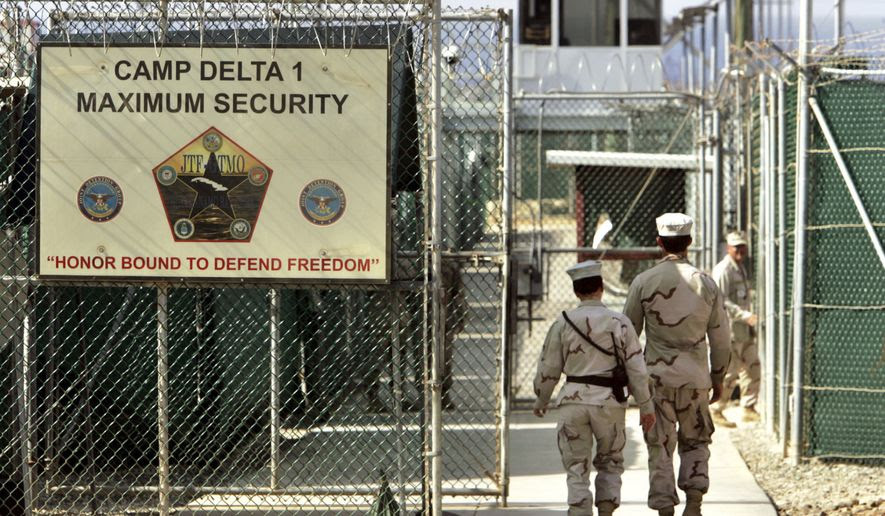 FILE - In this June 27, 2006 file photo, reviewed by a US Department of Defense official, US military guards walk within Camp Delta military-run prison, at the Guantanamo Bay US Naval Base, Cuba. A draft executive order shows President Donald Trump asking for a review of Americas methods for interrogation terror suspects and whether the U.S. should reopen CIA-run black site prisons outside the U.S.  (AP Photo/Brennan Linsley, file)