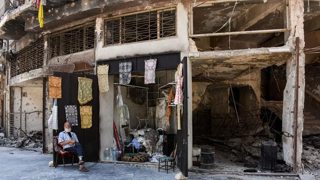 An elderly Syrian sits outside a newly reopened shop selling tablecloths amid the destruction of Aleppo's old city. Picture: AFP