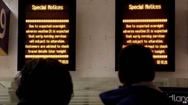 Rail passengers at Euston station looking at signs