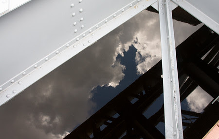 reflections of the sky through open bridge structure