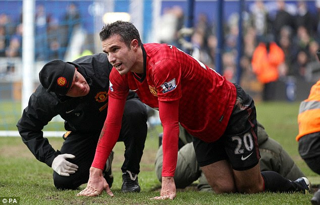 Concern: Robin van Persie receives treatment on the touchline after picking up an injury