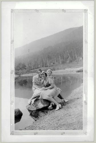 Three girls sitting on a rock