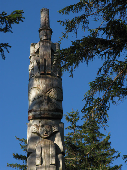 watchmen top the totem pole in front of Chief Son-i-Hat Whale House, Kasaan, Alaska