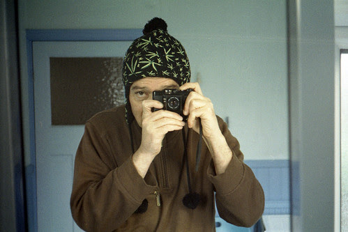 reflected self-portrait with Chinon Bellami camera and leaf-patterned hat by pho-Tony