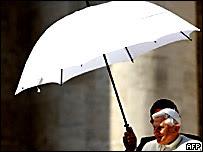Benedicto XVI es protegido con una sombrilla