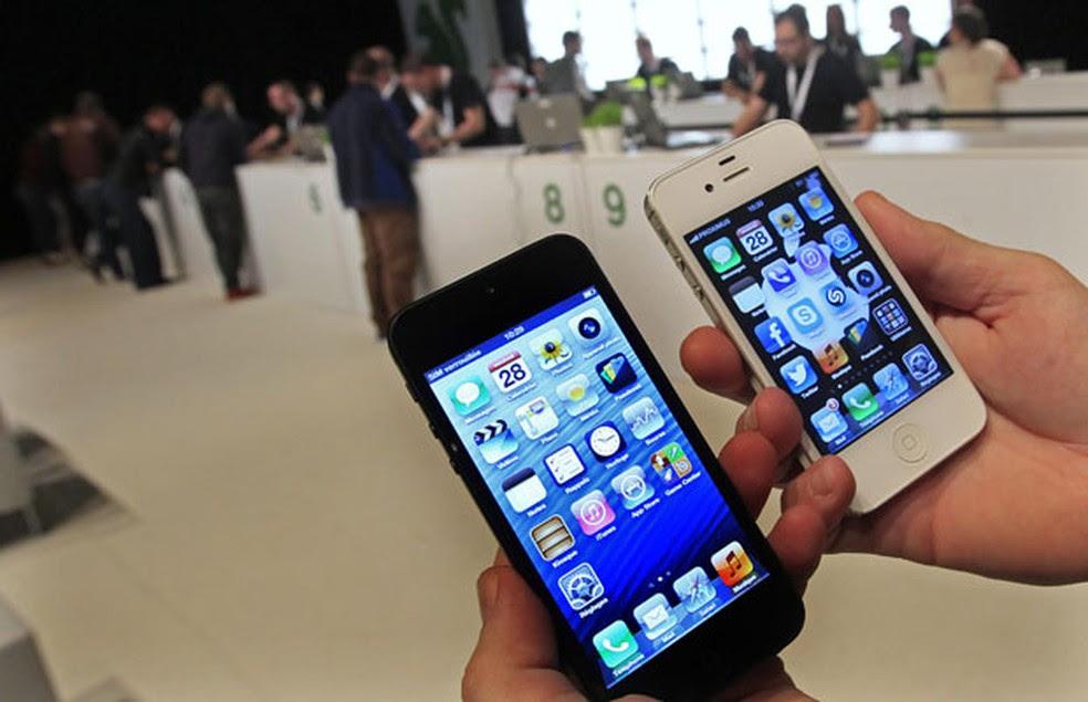 Usuário compara a nova versão do smartphone (à esquerda) com o iPhone 4S durante o lançamento do aparelho em Bruxelas. O novo iPhone está mais comprido, leve e fino. (Foto: Yves Herman/Reuters)