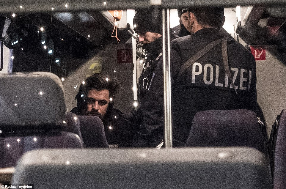Um suspeito olha como ele é levado em custódia pela polícia perto do local do ataque terror na noite passada.  Não está claro o que ele foi preso por
