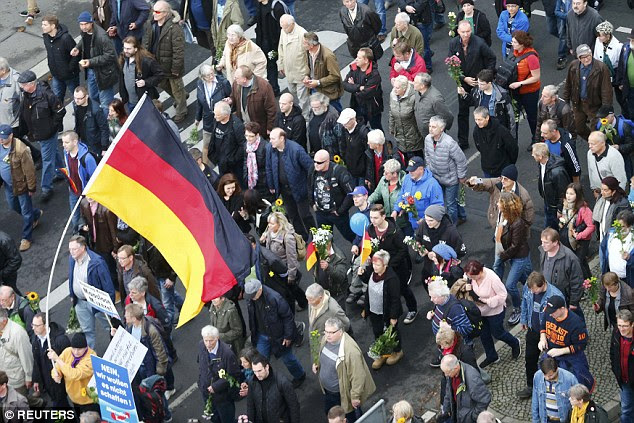 As well as waving red cards for Merkel, many protesters waved German flags and carried bunches of flowers