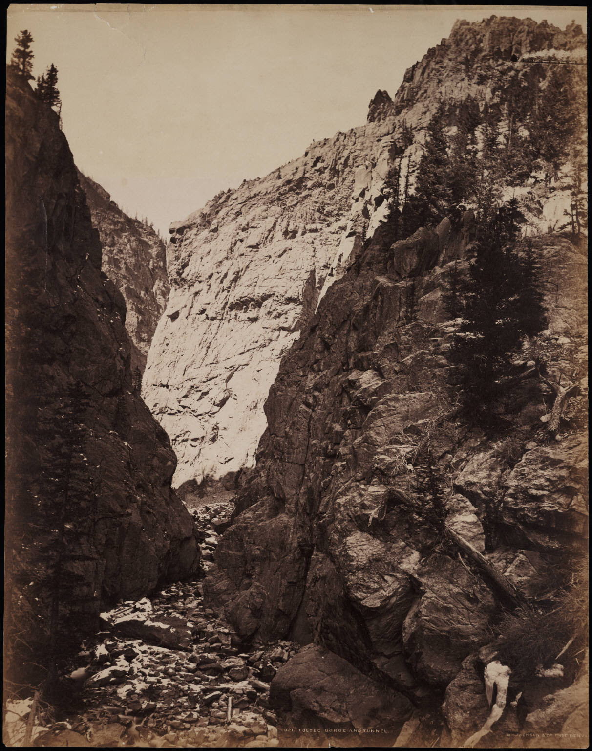[No. 1021. Rio de los Pinos, (Rio San Antonio) and rock formations in the Toltec Gorge, Rio Arriba County, New Mexico. Shows a Denver and Rio Grande Railroad train near the Toltec tunnel high on the rock cliff].