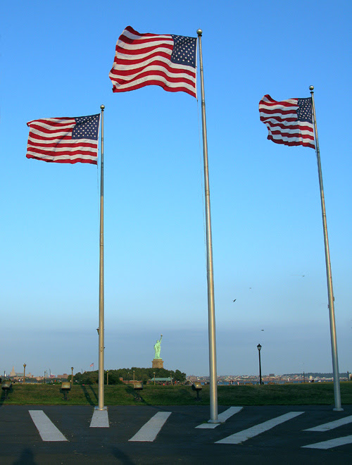 three American flags wave with the Statue of Liberty in the background, Liberty State Park, NJ