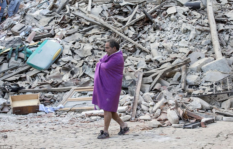 A man covered in a blanket walks in front of the rubble appears to walk in children's shoes after escaping the earthquake