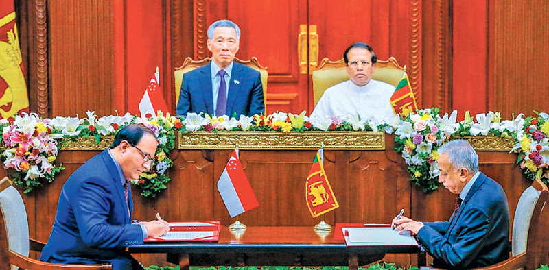 Development Strategies and International Trade Minister, Malik Samarawickrema and Singapore Trade and Industry Minister, S. Iswaran signing the Free Trade Agreement on behalf of their respective governments, in the presence of President Maithripala Sirisena and Prime Minister Lee and Prime Minister Wickremesinghe. Pictures by Sudath Silva