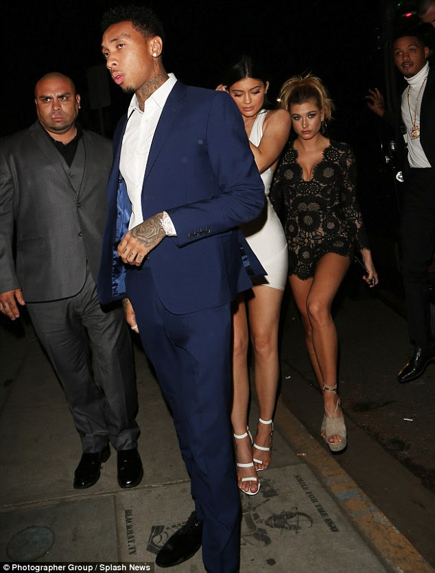 Her crew:She was also in the company of Kylie, who changed out of her black leather and chain bondage style dress into a plunging white bandage dress with matching heels