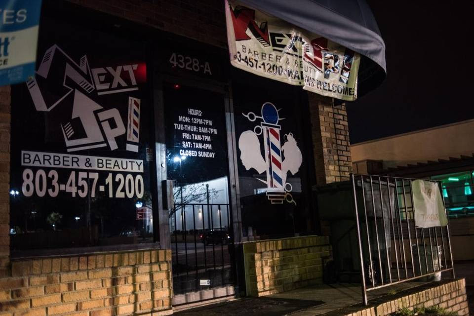 Headlights of a passing vehicle on Fort Jackson Boulevard illuminate Next Up Barber & Beauty on Saturday night in Columbia. One of two masked men who allegedly robbed patrons at the shop Friday night was shot and killed when two of the patrons pulled weapons and shot back, Columbia police said. January 23, 2016