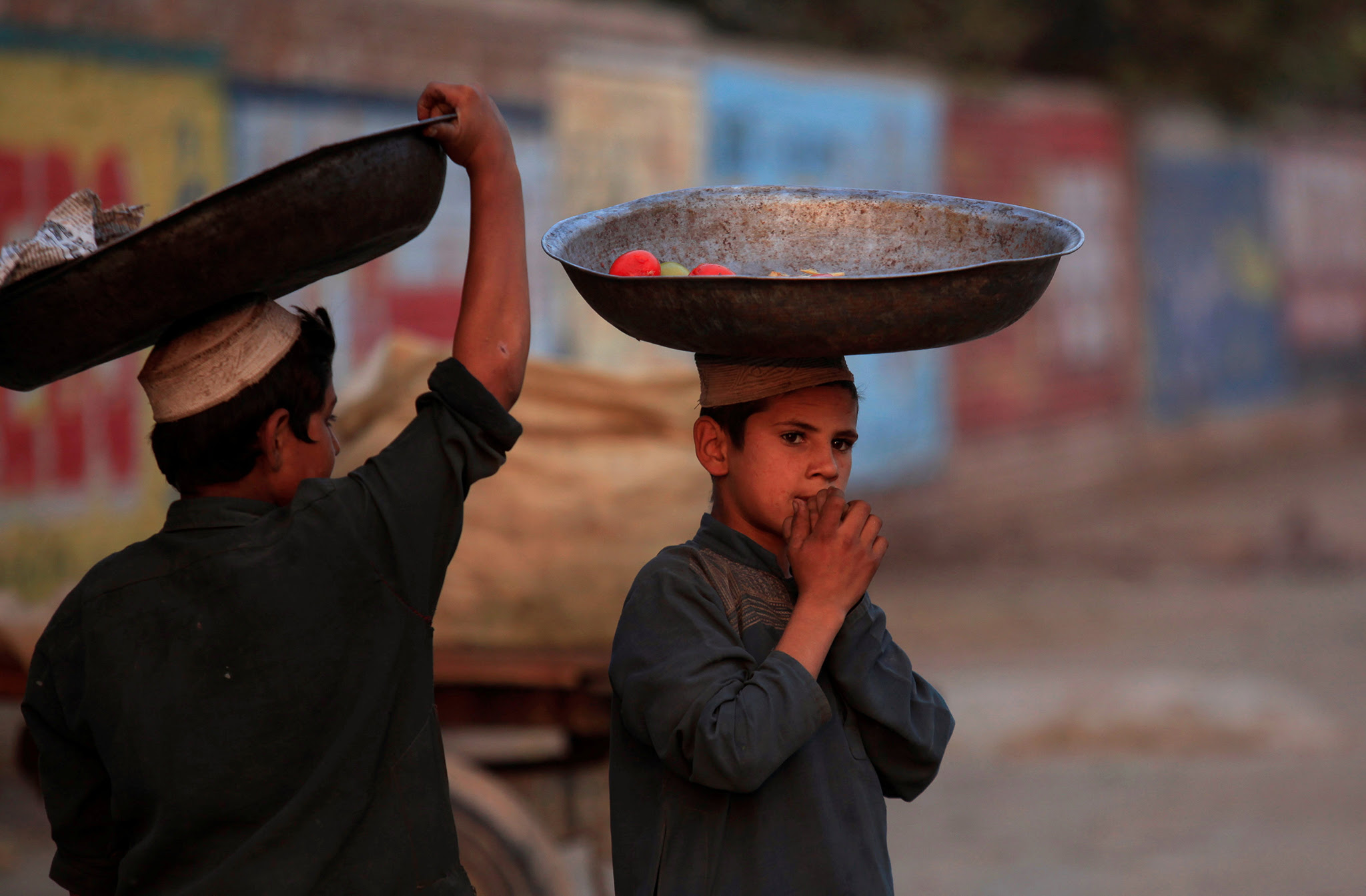 Boys wait to collect vegetables from a pile of rotten vegetables near a dustbin in Peshawar, Pakistan November 10, 2016 REUTERS/Fayaz Aziz