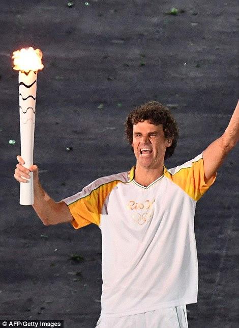 tenista brasileiro Gustavo Kuerten trouxe a chama para o estádio e passou para medalhista de basquete prata 1996 das mulheres Olímpicos Hortência Marcari que o deu a De Lima.