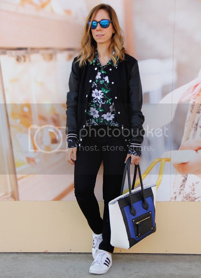 Fashion blogger The Key To Chic wears an Equipment floral silk blouse, Forever 21 faux leather varsity jacket, J Brand skinny jeans in black, Mossimo colorblock handbag, and Adidas superstar 2 sneakers.