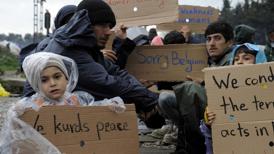 March 23, 2016: Refugees and migrants hold placards during a protest demanding the opening of the Greek-Macedonian border. (Reuters)
