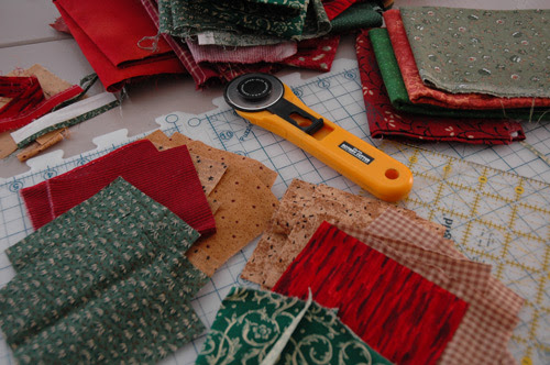 """I wanted to use fabric from the stash. I didn't want to use very light backgroud as I do inted to use this quilt for a lap quilt. I always dreamed of a quilt for X-mas, and looking at my stash, I started to pick out the green and the reds, - mostly from the selection I've named """"country"""" in my head."""