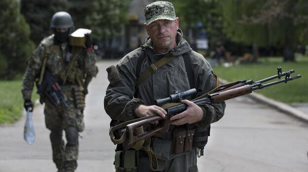 Pro-Russian gunmen carry their weapons in the center of Slovyansk, Ukraine, Tuesday. Gun battles were fought around the city Monday in what has proven the most ambitious government effort to regain control of areas taken by separatists.