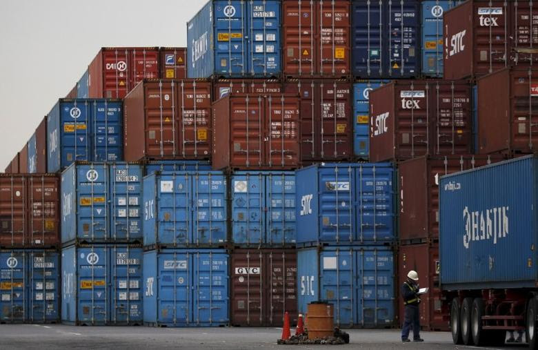 A laborer works in a container area at a port in Tokyo, Japan, March 16, 2016. REUTERS/Toru Hanai