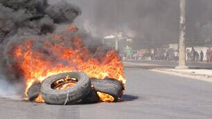 Tires set alight by mobs protesting rising food prices burn in a street in Maputo, Mozambique, on Wednesday.
